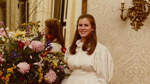 Susan wearing a white dress with long auburn hair stands next to a big bunch of flowers in front of a mirror at her debut.