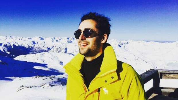 Tom on a ski slope wearing a yellow jacket and sunglasses.