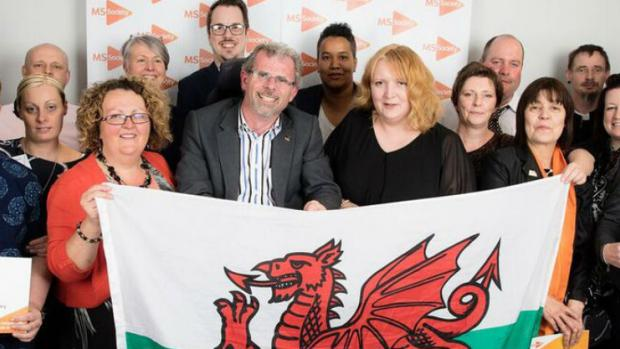 A group of people in Wales holding a Welsh flag