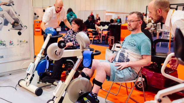 Chair user Glyn does leg strengthening exercises with others with MS