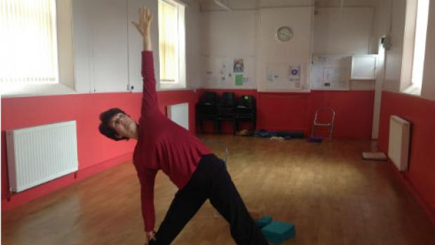 Image shows Yvette practicing yoga