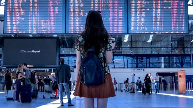 A young woman looks at a giant airport departure board