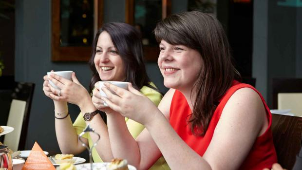Photo shows two women drinking cups of tea at an MS Society Cake Breaks