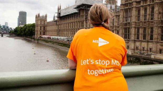 Photo shows a woman on a bridge outside the Houses of Paliament wearing a t-shirt that says Let's stop MS together