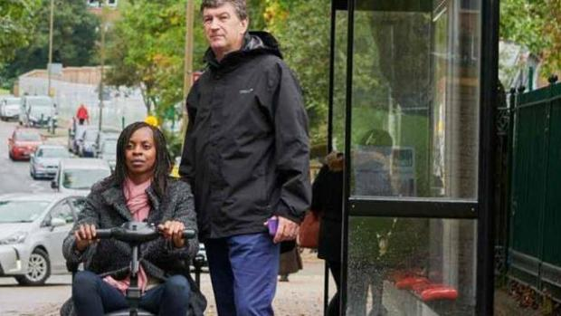 Photo: Woman with MS waiting for a bus with her husband