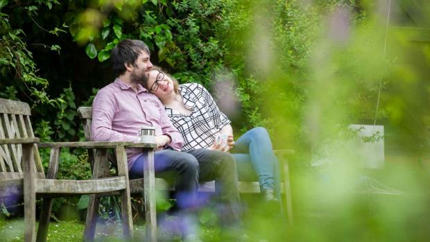 a Couple in garden sat on a bench
