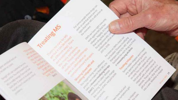 Photo: Man reading MS information booklet closeup