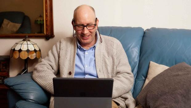 a man sat on a sofa using a laptop smiling