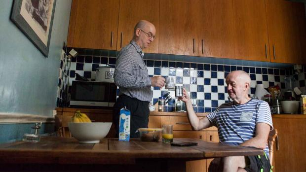 Photo: Men sat in kitchen