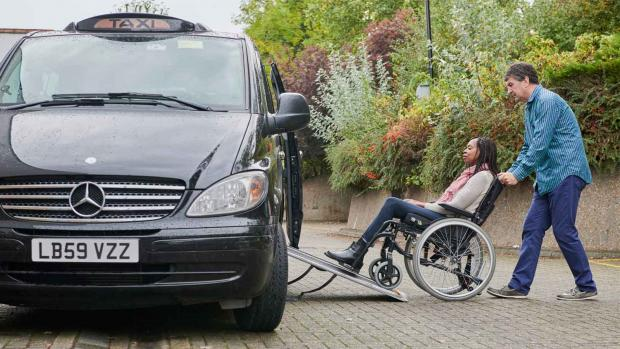 a photo of a Woman in awheelchair getting into taxi