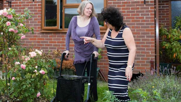 Photo: Two Women talking  in a garden