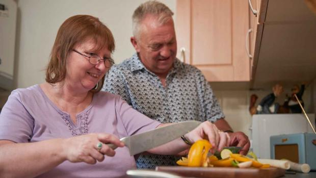 Photo: Woman with MS preparing healthy food at home with husband