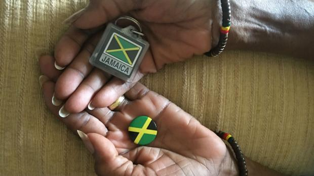 Image shows the hands of Karen's mum, holding a Jamaican badge and key ring and wearing bracelets showing Jamaican colours.