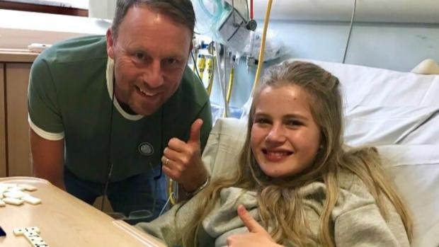 Lucy sits in a hospital bed. Her dad is by her side. They are both doing thumbs up.