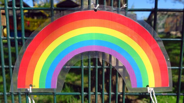 Paper rainbow coloured in fixed to a playground gate with string