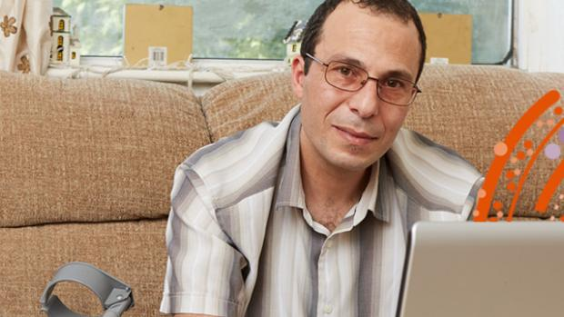 man at home sitting on his sofa, with a laptop in front of him