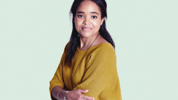 Chandra wearing a yellow jumper against a light blue background