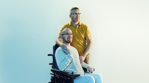 Glyn, using a wheelchair, with his husband Mark, standing.