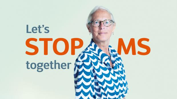 Image text says 'Let's stop MS together' behind Jacqueline who is standing in front of blue background wearing a blue and white dress
