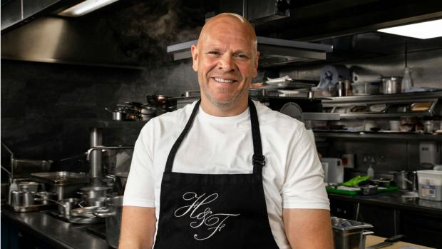 Tom Kerridge in his kitchen wearing an apron and smiling