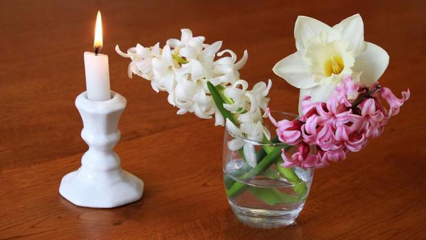White candle burns in a china holder next to a glass of spring flowers