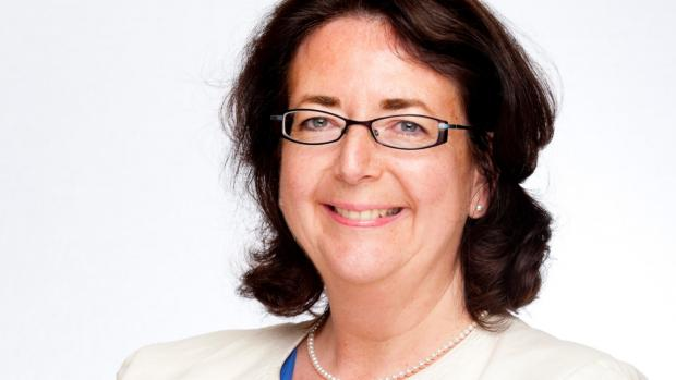 Professor Parvitt stands against a white background. She has shoulder length brown hair, is wearing glasses and is smiling.