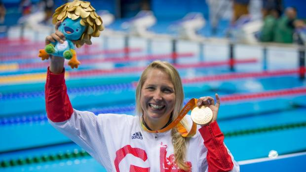 Stephanie picture by pool in Rio at Paralympics holding up gold medal and smiling