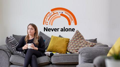 Woman sitting on a grey sofa holding a cup of tea with an orange rainbow and the words never alone behind her