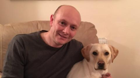 Image shows blogger Chris sat on a sofa with his dog
