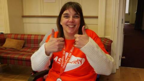 A volunteer giving the thumbs up