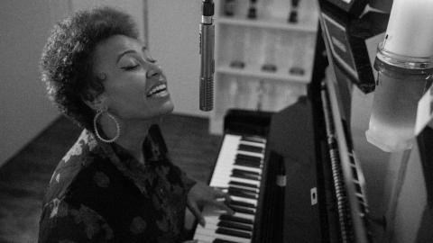 a photo in black and whote of Emeli Sande playing piano