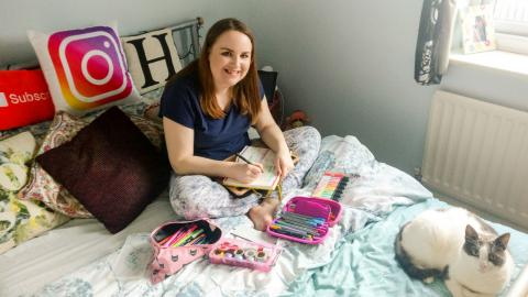 Photo: Hannah sitting on her bed writing her bullet journal.