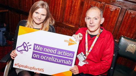 Holly and George at parliament event holding Ocrelizumab placard