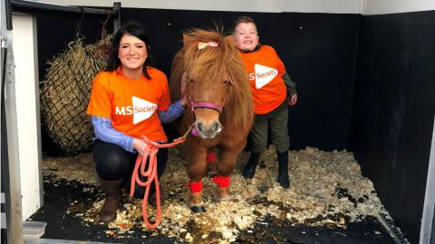 Shirley with Winnie the Shetland Pony and her son Joseph.  Shirely and Jospeh are wearing MS Society t-shirts and Wnnie has an orange bow in her hair.