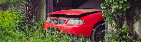 a red car in a garage in a field