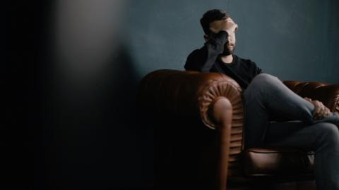 Man sitting in a dark room with one hand on is forehead
