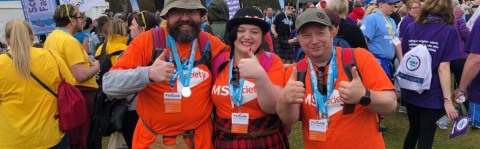 Two men and a woman take a moment out from the crowd, all wearing hats, MS Society shirts and kits smile with thumbs up at the camera sporting their medals for completing the Kiltwalk