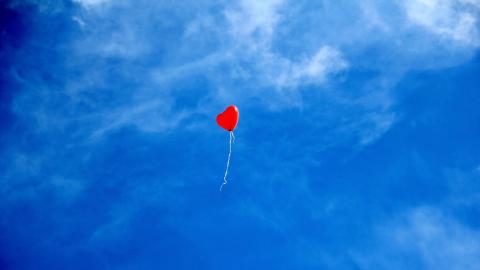 Heart shaped balloon floating in blue sky