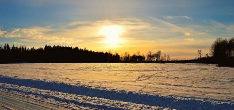 The sun sets over a field of snow