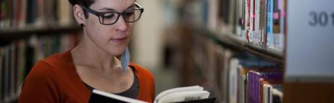 Photo: Woman with MS reading book in library