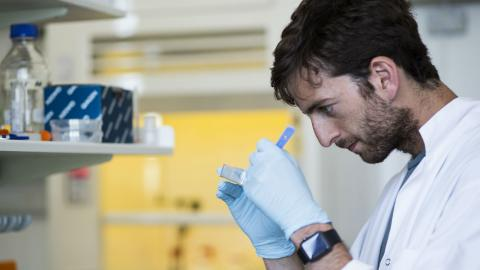 A young male scientist wearing a white lab coat and gloves works intently in a research lab.