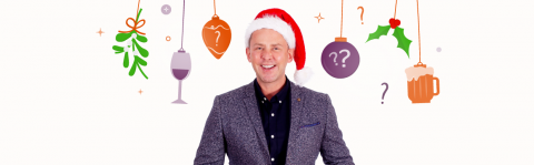 Scott Mills wearing a Christmas hat with festive graphics in the background